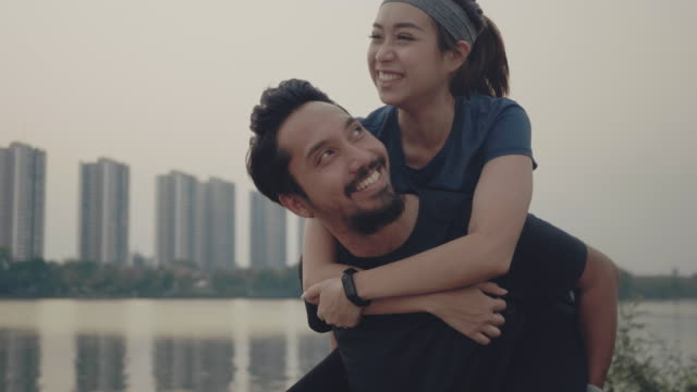 公園で遊んでいる間、週末を楽しむアジアのカップル - 談笑する点の映像素材/bロール
