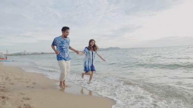 vídeos y material grabado en eventos de stock de pareja asiática sintiéndose feliz en la playa. - idyllic