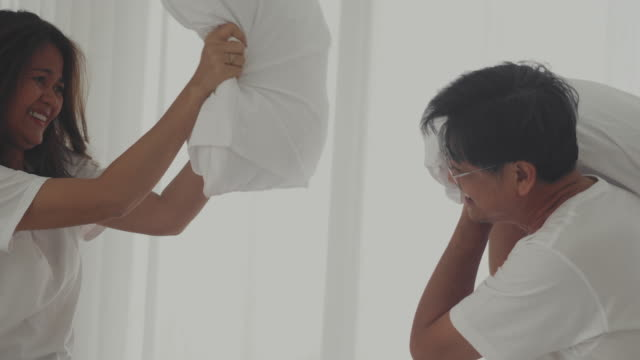 asian couple having a pillow fight in the morning - bedding stock videos & royalty-free footage