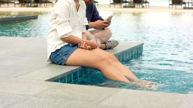 HD DOLLY : asian couple having relax beside the pool