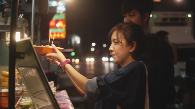 asian couple having the date on street food. - girlfriend stock videos & royalty-free footage