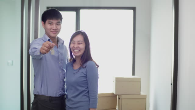 asian couple holding key house,  showing keys buying new apartment looking at camera - computer key stock videos & royalty-free footage
