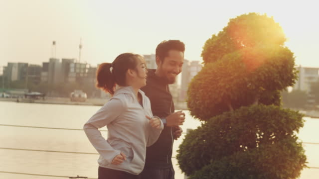 asian couple jogging in sunset. - ponytail stock videos & royalty-free footage