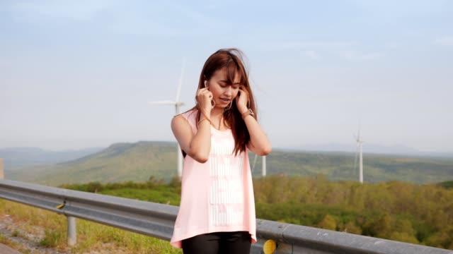 vídeos y material grabado en eventos de stock de pareja asiática de jogging o correr en el campo de turbinas eólicas en la madrugada. healty concept. escuchar música y utilizar reloj inteligente mientras se ejecuta. - corredora de footing