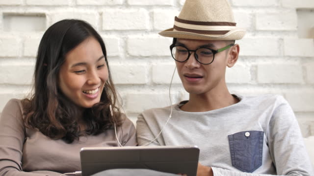 Asian Couple listening to music on Tablet PC