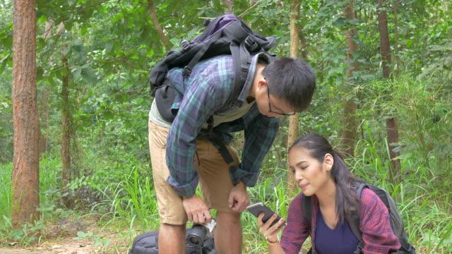Aziatische paar op zoek kaart en mobiele telefoon in het bos.