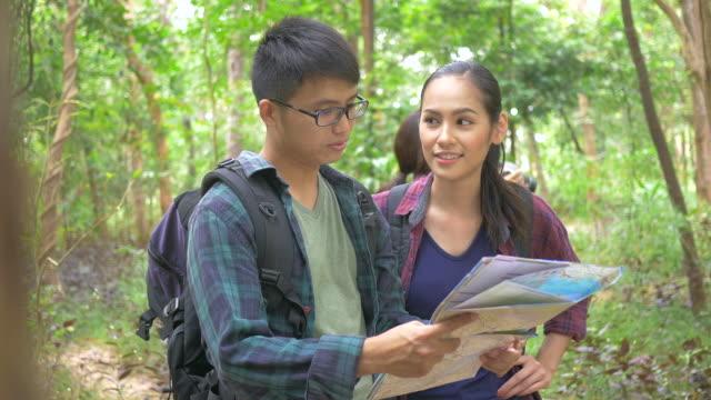 Aziatische koppel op zoek kaart en wandelen in het bos.
