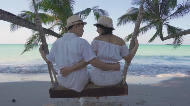 stockvideo's en b-roll-footage met aziatische paar minnaar in witte jurk geniet van huwelijksreis en lange vakantie op het strand van de zee, zittend op de schommel samen ontspannen en comfortabel, valentijn. zomer, reizen, vakantie en vakantie concept. - witte jurk