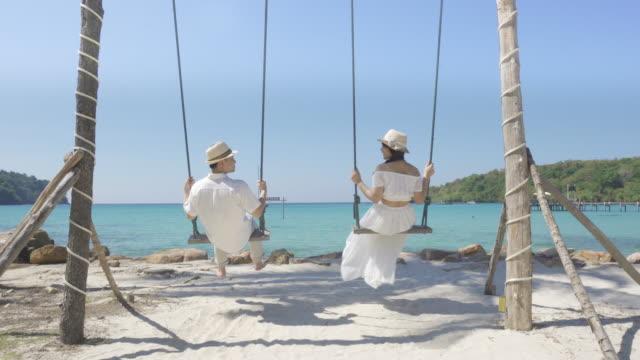 stockvideo's en b-roll-footage met aziatische paar minnaar in witte jurk geniet van huwelijksreis en lange vakantie op het strand van de zee, siiting op de schommel samen ontspannen en comfortabel, valentijn. zomer, reizen, vakantie en vakantie concept. - witte jurk