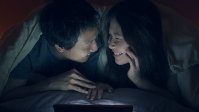 asian couple lying and watching tablet on bed together at nighttime - blanket stock videos & royalty-free footage