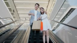 Asian Couple on an Escalator in a Shopping Mall
