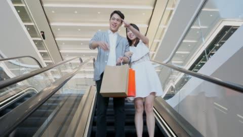 vídeos y material grabado en eventos de stock de pareja asiática en una escalera mecánica en un centro comercial - gran almacén