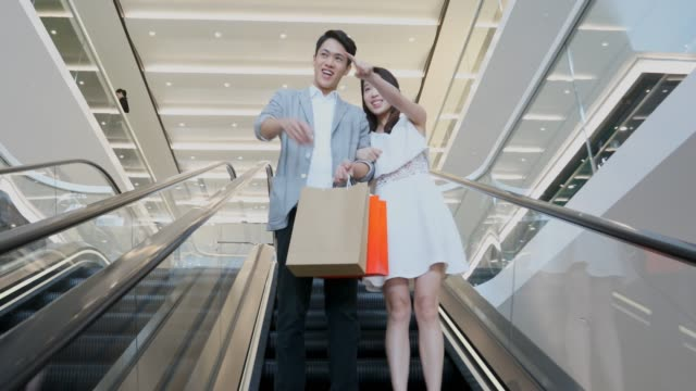 asian couple on an escalator in a shopping mall - shopping mall stock videos & royalty-free footage
