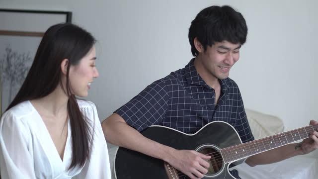 stockvideo's en b-roll-footage met aziatisch paar dat een akoestische gitaar speelt en in gezellige slaapkamer zingt - jong van hart