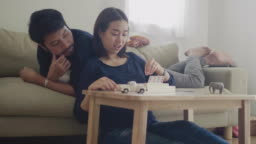 Asian couple playing game together at home with happy emotion
