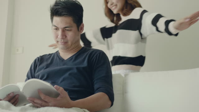 Asian couple reading together on the sofa.