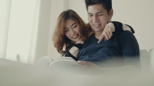 asian couple reading together on the sofa. - magazine stock videos & royalty-free footage