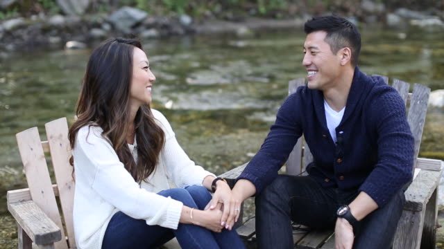 asian couple relax and embrace in forest creek setting, chairs - eskapismus stock-videos und b-roll-filmmaterial