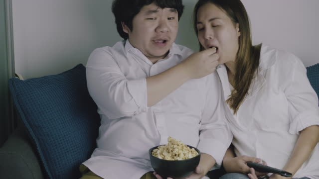 Asian couple relaxing indoors watching television together