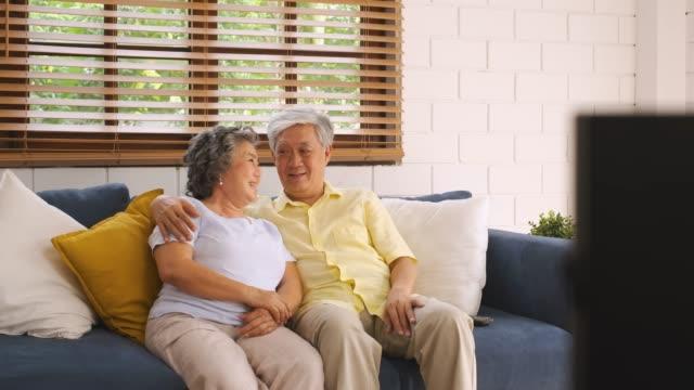 stockvideo's en b-roll-footage met aziatisch paar senior zittend op sofa tv kijken in de woonkamer thuis. panning van blur voorgrond televisie. - woongemeenschap ouderen