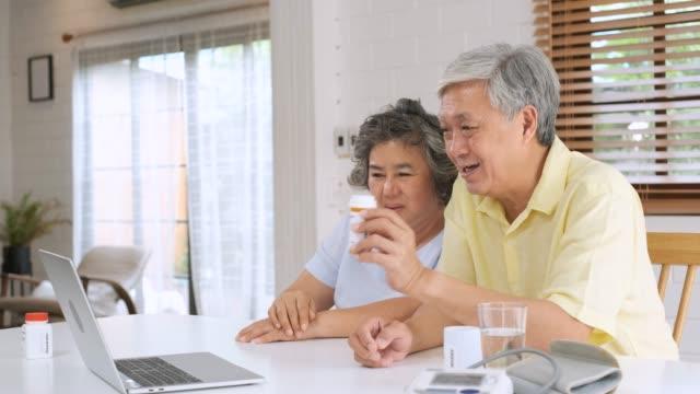vídeos y material grabado en eventos de stock de asiático pareja seniors uso portátil video conferencia con médico sobre la enfermedad y píldora de prescripción en la sala de estar en casa. estilo de vida saludable. envejecimiento en el concepto de casa - oriental asiático e indio