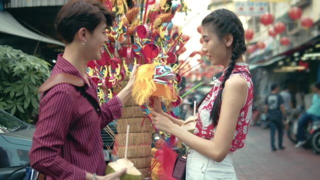 asian couple shopping at street market in chinatown bangkok, thailand. - souvenir stock videos and b-roll footage