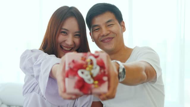 カメラへの贈り物を示すアジアのカップル - 見せる点の映像素材/bロール