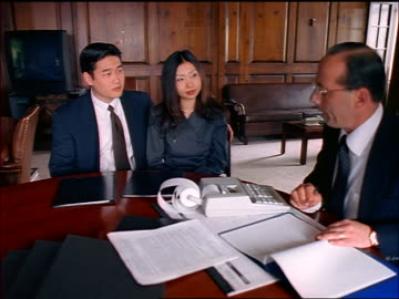 asian couple sits at table with male financial advisor/lawyer / he gives them papers + they sign - addierrolle stock-videos und b-roll-filmmaterial