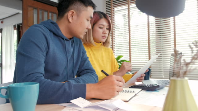 asian couple sitting at table in kitchen calculate home budget with paper bill and laptop in new house. - calculator stock videos & royalty-free footage