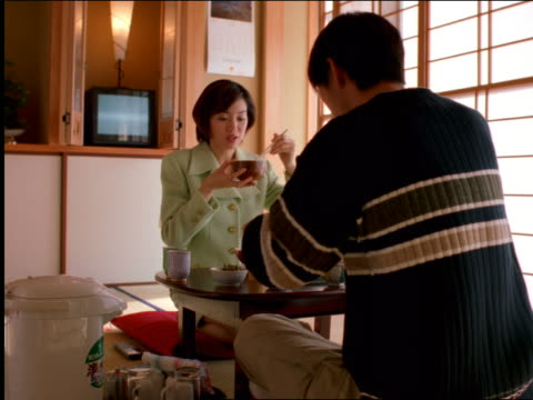 Asian couple sitting on floor at table talking + eating with chopsticks / Tokyo, Japan