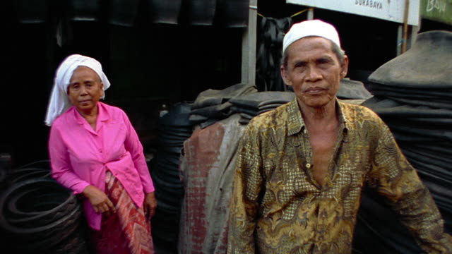 ms portrait asian couple (merchants) standing in middle of stacked tires / java, indonesia - indonesian ethnicity stock videos & royalty-free footage