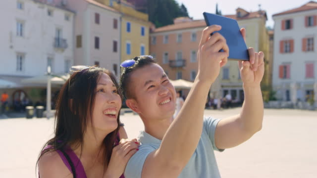 Asian couple taking a selfie with a tablet on a square of a coastal town