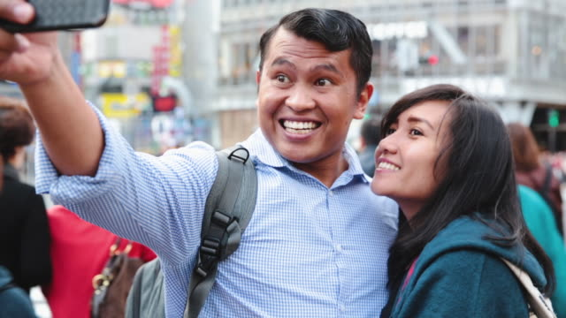 asian couple taking selfie at shibuya crossing in tokyo - mid adult couple stock videos & royalty-free footage