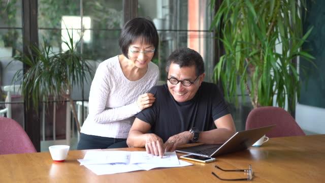 vidéos et rushes de couples asiatiques parlant de la conception de leur nouvelle maison - 60 64 ans