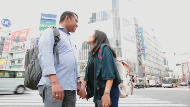 asian couple talking at shibuya crossing in tokyo - mid adult couple stock videos & royalty-free footage