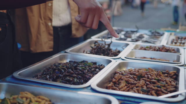 asian couple tourists buying fired insects at street food. - esotismo video stock e b–roll