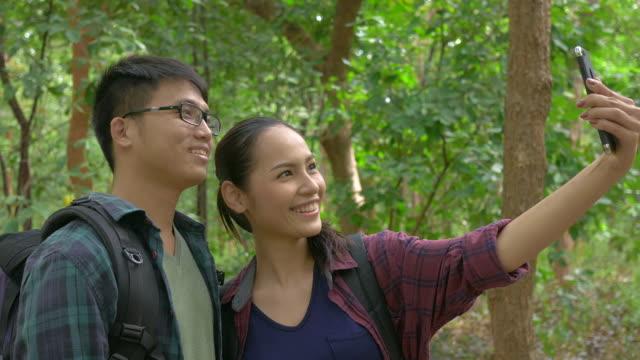 Aziatische paar reizen buiten levensstijl nemen fotografische met mobiele telefoon in bos