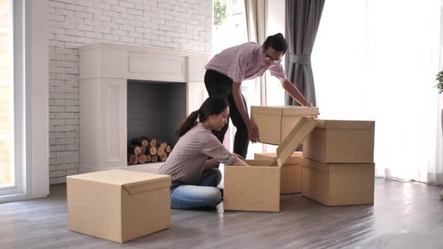 vídeos de stock, filmes e b-roll de casal asiático desempacotar caixas na nova casa no dia em movimento - família jovem