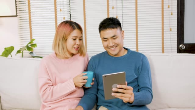 asian couple use tablet and drink coffee at safa in living room at home - coffee drink stock videos & royalty-free footage