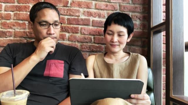 vidéos et rushes de couples asiatiques utilisant la tablette d'ordinateur dans le café - centre culturel