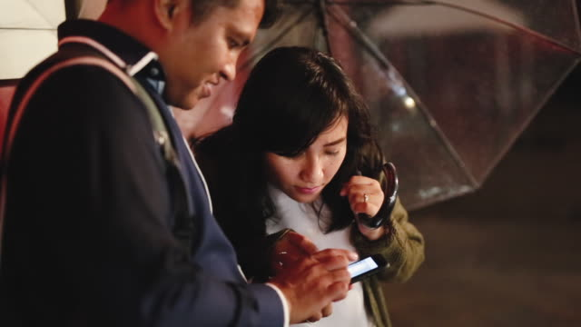 asian couple using smart phone in the street at night in tokyo - mid adult couple stock videos & royalty-free footage