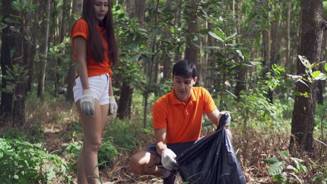 coppia asiatica volontaria raccoglie immondizia nei parchi concetto di protezione ambientale. - sollevare video stock e b–roll