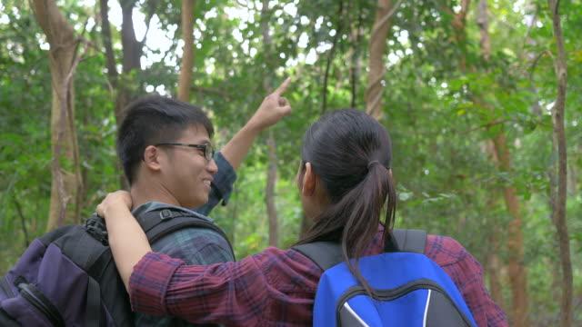 Aziatische paar wandelen in het bos. Aziatische man en vrouw reizen buiten levensstijl in bos