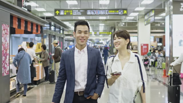 asian couple walking through airport - mid adult couple stock videos & royalty-free footage