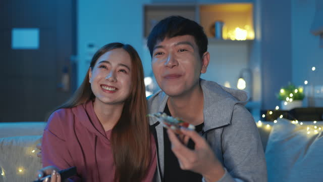 asian couple watch tv happily - remote control stock videos & royalty-free footage