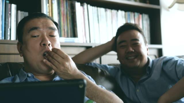 朝のデジタル タブレットを見てアジア カップル - ゲイ点の映像素材/bロール