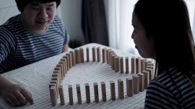 Asian couple with relaxing time with their activity of making jigsaw of heart shape to present valentine concept with leisure activity