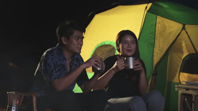 asian couples drink coffee together at night. relaxation camping, weekend activities - coffee drink stock videos & royalty-free footage