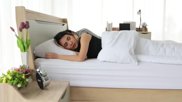 stockvideo's en b-roll-footage met aziatische parenminnaar die wakker wordt en wekker in haar bed sluit volledig rustte in ochtend - dekbed