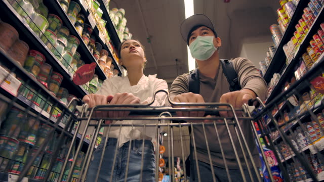 asian couples shopping in supermarket - cibi surgelati video stock e b–roll